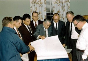 From left right: - Sam Tinker (?) with back to camera; Ned Boring; Gene Dickey; Mr. Bruce (?); Zeke Leslie (folding blueprints); Arden Taylor; Lynwood Stapleton; Warren Granger.